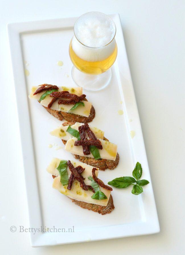 borrelplank met old white geitenkaas, pesto, zongedroogde tomaat en bier