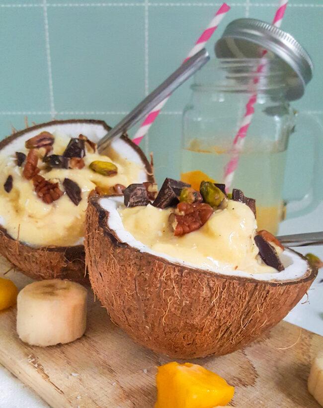 recept voor een tropisch dessert in een kokosnoot met banaan en mango