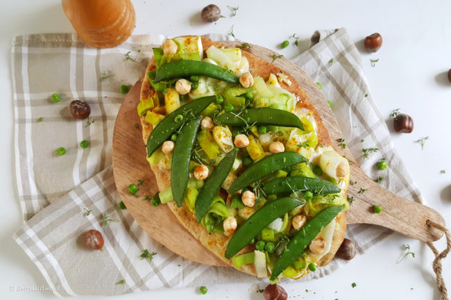 Naan pizza met groene groenten, brie en hazelnoot